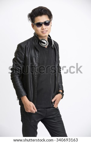 Smiling smart young man in urban style with headphone and eye wear on white. - stock photo