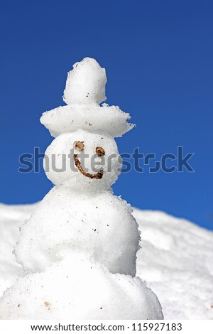 smiling snowman in a snow field, against blue sky - stock photo