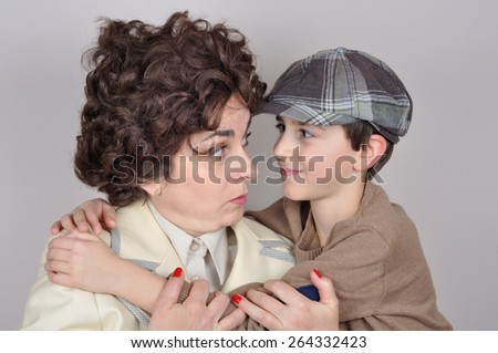 Smiling son with tartan newsboy cap hugging his surprised and angry mother. They are looking at each other. Isolated on the gray background. Vintage style photo - stock photo