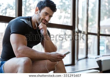 Smiling sportsman wearing black t-shirt listening to music - stock photo