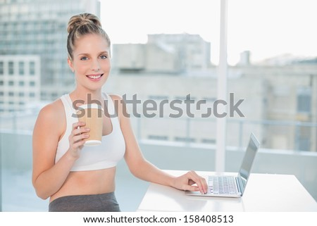 Smiling sporty blonde using laptop holding coffee in bright room - stock photo