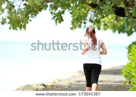 Smiling Sporty female runner jogging on beach. - stock photo
