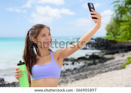 Smiling sporty woman taking selfie using smartphone on beach. Beautiful fit fitness female in sports bra is holding water bottle. Attractive young woman is posing at sea shore. - stock photo