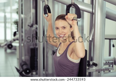 Smiling sporty young woman in a gym working out toning and strengthening her muscles with counter weights in a healthy lifestyle and fitness concept - stock photo