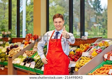 Smiling store manager in a supermarket holding his thumbs up - stock photo