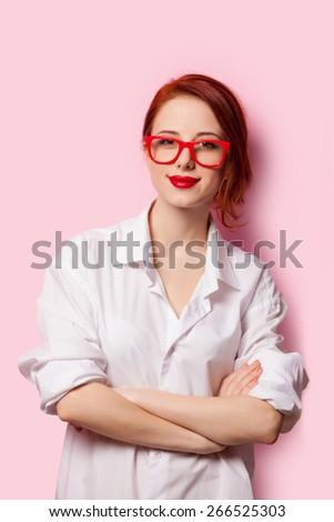 Smiling student girl in white shirt and red glasses on pink background - stock photo