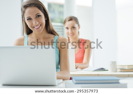 Smiling student girls at school sitting at desk in the classroom and using laptops, technology and education concept - stock photo