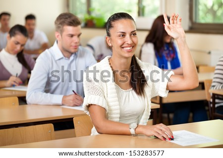 Smiling student giving answer in class with his hand raised - stock photo
