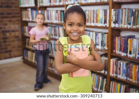 Smiling student holding a few books at the elementary school - stock photo