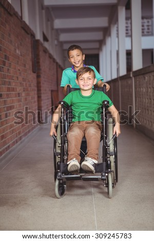 Smiling student in a wheelchair and friend pushing on the elementary school grounds - stock photo