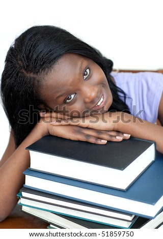 Smiling student leaning on a stack of books against a white background - stock photo