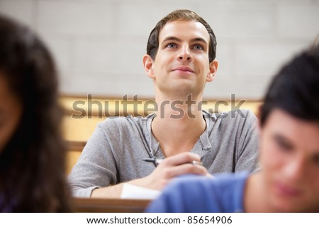 Smiling student listening to a lecturer in a amphitheater - stock photo