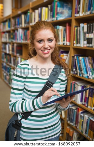 Smiling student using tablet standing in library at the university - stock photo