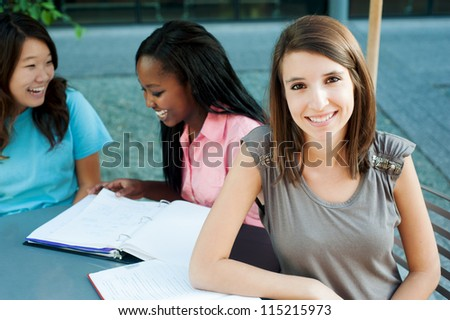 Smiling student with friends in the background - stock photo