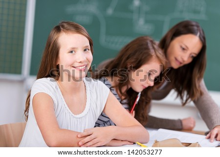 Smiling student with her classmate listening to teacher in school classroom - stock photo