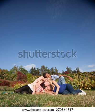 Smiling students lay on grass across beautiful park and deep blue sky and show unity - stock photo