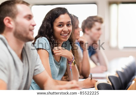 Smiling students listening a lecturer in an amphitheater - stock photo