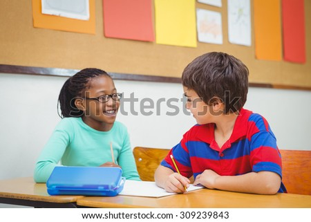Smiling students looking at each other at the elementary school - stock photo
