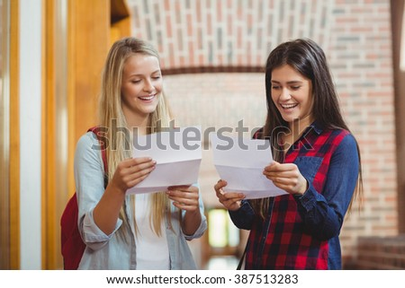Smiling students looking at results at university - stock photo