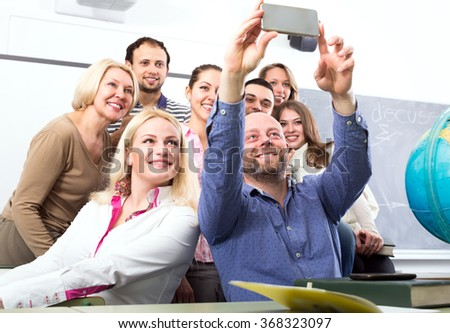 Smiling students posing in a classroom while their lecturer is taking a group selfie with his phone - stock photo