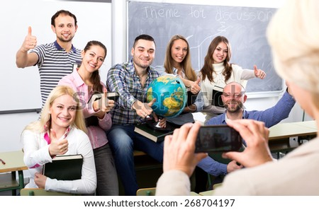 Smiling students posing with textbooks, thumbs upm a globe while their teacher is taking a photo of them with a phone - stock photo