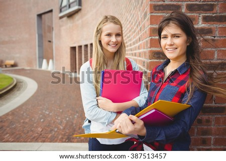 Smiling students reading book at university - stock photo