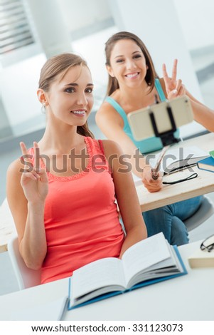 Smiling students sitting at school desk and taking selfies using a smart phone and a selfie stick, they are making v signs - stock photo