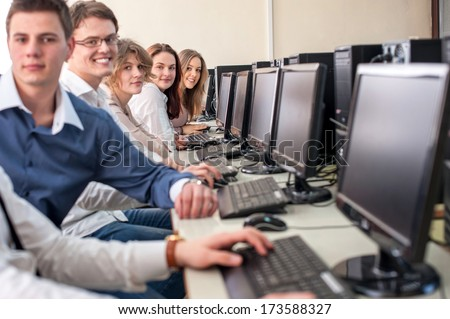 Smiling students sitting by computers in schoolroom - stock photo