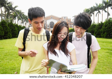 smiling students standing together with books at a campus - stock photo