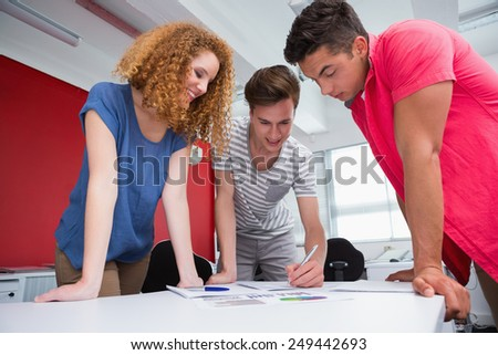 Smiling students working and taking notes together at the college - stock photo