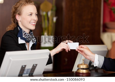 Smiling stylish beautiful receptionist handing over a blank white card to a client at the reception desk - stock photo