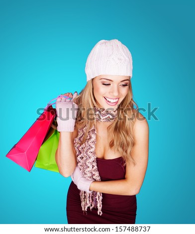 Smiling stylish beautiful young woman in a knitted cap, scarf and gloves with shopping bags held over her shoulder on a blue background - stock photo