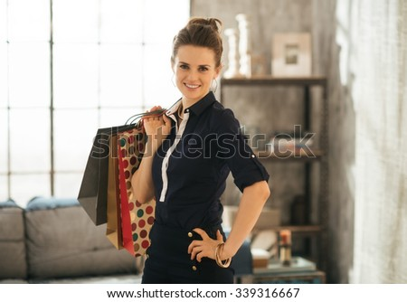 Smiling stylish brunette woman in elegant clothing is standing in loft living room and holding shopping bags. Good shopping spree makes any woman happy. Luxurious life concept - stock photo