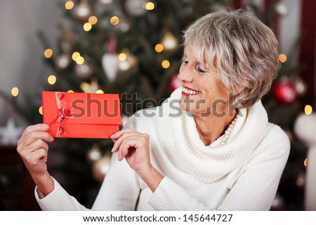Smiling stylish elderly woman displaying a red Christmas voucher in her hands in front of a twinkling Christmas tree - stock photo
