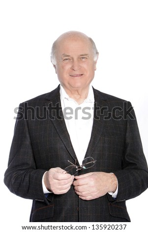 Smiling stylish pensioner in a jacket holding his glasses in his hands, upper body studio portrait isolated on white - stock photo