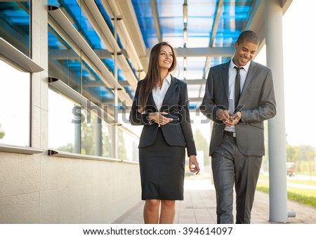 smiling successful business man and woman outdoors, , over office building  - stock photo
