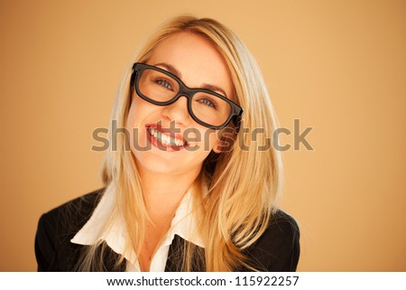 Smiling successful businesswoman wearing glasses, head portrait on a brown studio background - stock photo