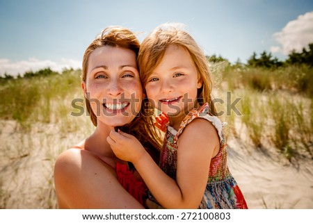 smiling summertime family on the beach - stock photo