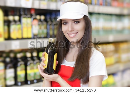 Smiling Supermarket Employee Holding a Product - Portrait of a young sales clerk in a market store  - stock photo
