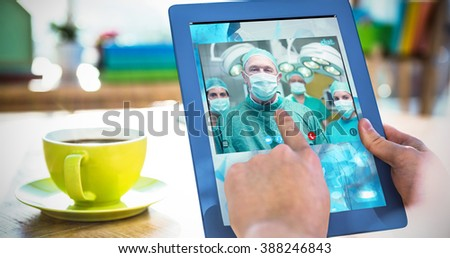Smiling surgeon posing with a team against cropped image of hipster businessman using tablet - stock photo