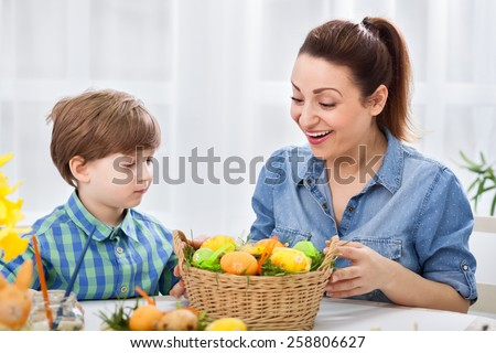 Smiling surprised family looking at colored easter eggs - stock photo