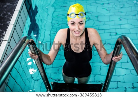 Smiling swimmer woman getting out of the swimming pool wearing swimming hat - stock photo