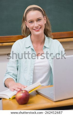 Smiling teacher at her desk at elementary school - stock photo