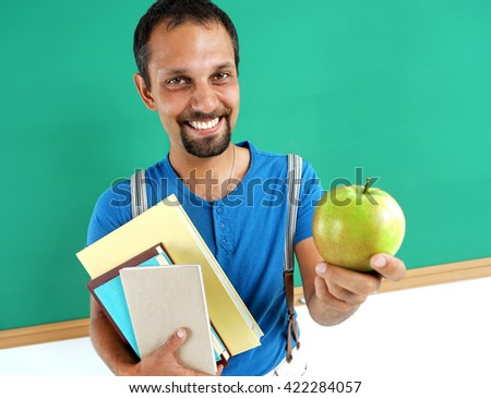 Smiling teacher hugging books and holding an apple. Creative concept with Back to school theme - stock photo