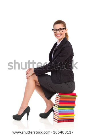 Smiling teacher is sitting on the stack of books. Full length studio shot isolated on white. - stock photo