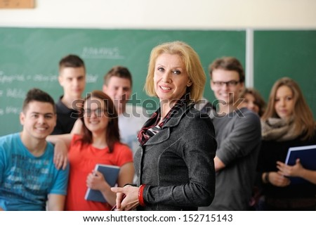 Smiling teacher standing in a classroom with students behind her - stock photo