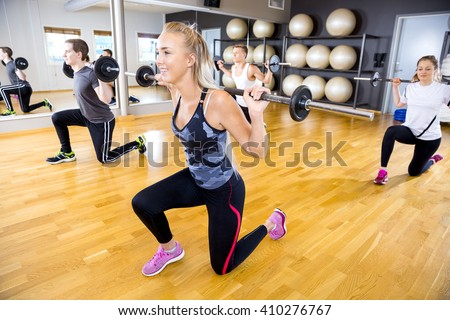 Smiling team doing split squats with weights at fitness gym - stock photo