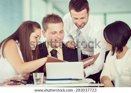 Smiling team of business people working together in company - stock photo