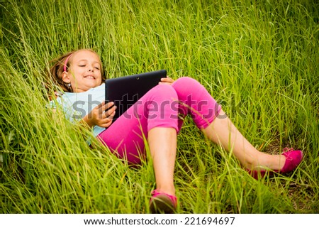 Smiling teen girl lying in grass and watching tablet - stock photo