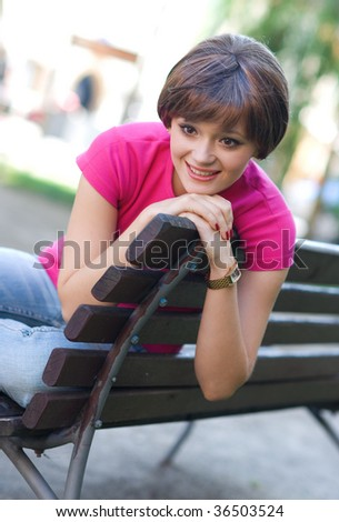 smiling teen girl on the park bench - stock photo
